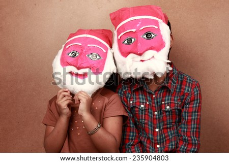 Two kids wear hand made masks of Santa - stock photo