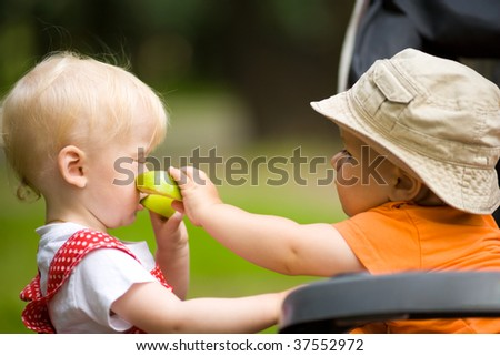 Two kids with apples outdoors looking after each other - stock photo