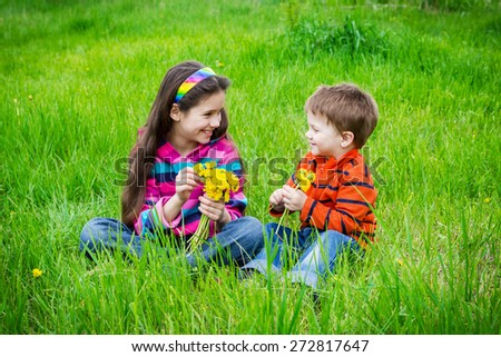 Two kids with bouquet of dandelions on green grass, meadow - stock photo