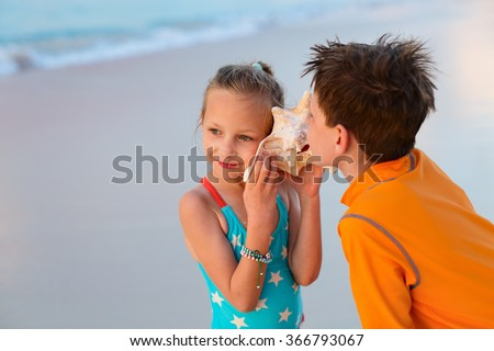 Two kids with giant shell at beach listening to the sea - stock photo