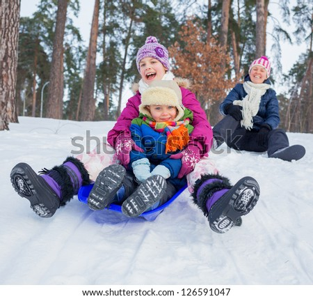Two kids with mother is sledging in winter-landscape. Focus on the boy. - stock photo