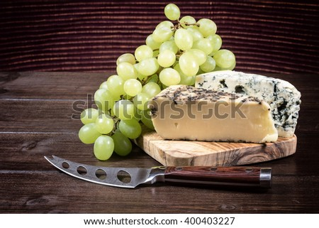 Two kinds of cheese and grapes of the white wine are lying on the board of olive wood. Stainless steel cheese knife is lying on a wooden board in foreground. Photo is edited as an vintage. - stock photo