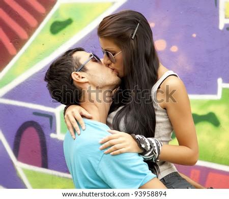 Two kissing near graffiti. - stock photo