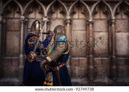 Two knights fighting aganist medieval cathedral wall. - stock photo