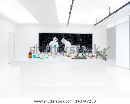Two lab technicians working in a laboratory with vials wearing masks. - stock photo
