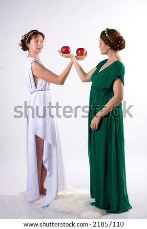 Two ladies in antique dress and two apples on white background - stock photo