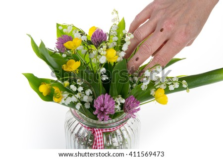 Two ladybird or ladybugs on hands with wild flowers - stock photo