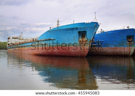 Two large rusty tankers  in Volga river at spring cloudy day - stock photo