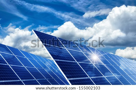 Two large solar panels under the blue sky with lively clouds, reflecting the sun - stock photo