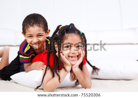 Two laughing children lie on the floor - stock photo