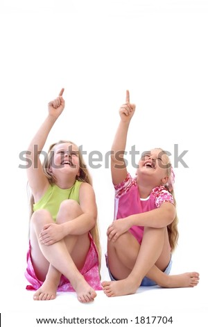 Two laughing girls, pointing towards.... your advertisement? - stock photo