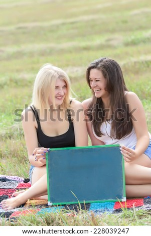 Two laughing student girls holding board for writing - stock photo