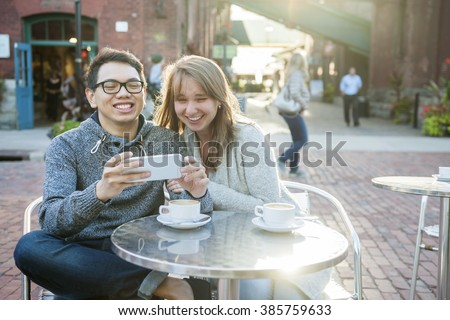 Two laughing young people looking into smartphone while sitting at a table in outdoor cafe - stock photo