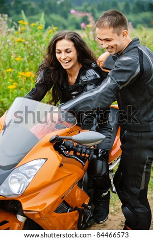 Two laughing young people: pretty brunette lady sitting on motorbike and handsome dark-haired man standing near. - stock photo