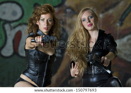 Two leather clad gun women aiming in the camera - stock photo