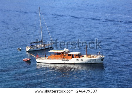 Two leisure boats anchored side by side - stock photo