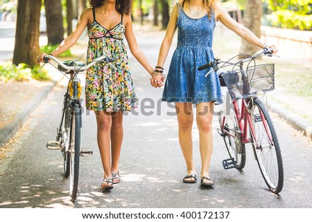 Two lesbian girls walking on the street. They are two women walking together and  holding their hands and a bike. Homosexuality and lifestyle concepts. - stock photo