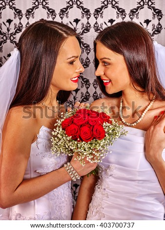 Two lesbians in wedding dresses hold bouquet of red roses . - stock photo