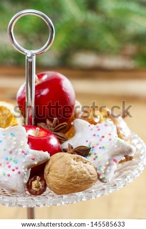 Two level dessert stand full of gingerbread cookies, apples, nuts, dried fruits and other christmas delicacy.  - stock photo