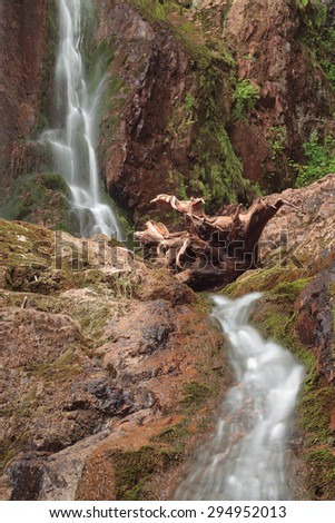 Two level waterfall with tree roots lying among the rocks. - stock photo