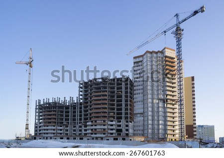 Two lifting crane and building under construction - stock photo