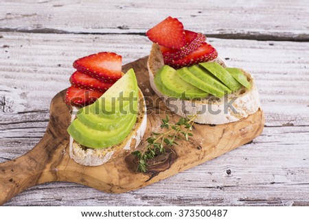 Two light mineral sandwich for breakfast lunch of homemade bread with avocado and strawberries served on the board of the olive tree. The concept of a simple natural healthy food. selective Focus - stock photo
