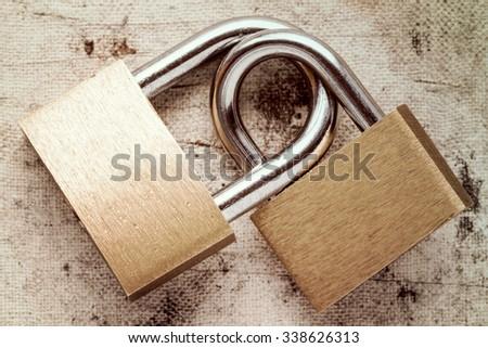 Two linked padlocks symbolizing good relationships or marriage - stock photo