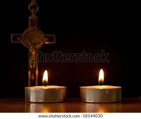 Two Lit Tea Candles with Crucifix in Background - stock photo