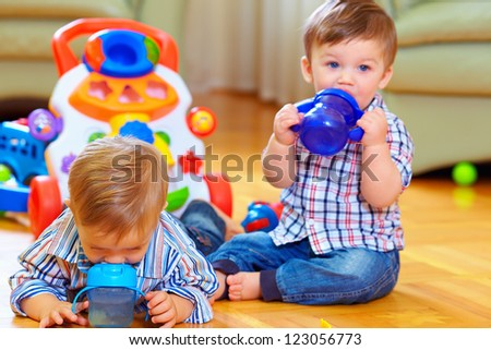two little baby boys drinking from feeding bottle, home interior - stock photo
