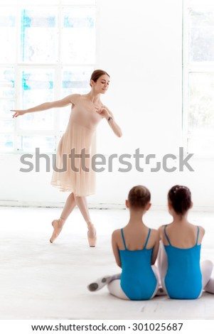 Two little ballerinas with personal ballet teacher in dance studio. classic ballet dancer as teacher posing on a white background. in the foreground the back girls - stock photo