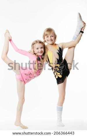 two little beautiful girls gymnasts doing exercises - stock photo
