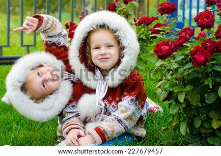 Two little beautiful sisters sitting next to flowers and hugging - stock photo