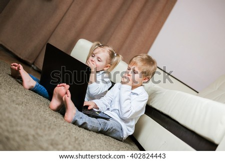 two little blond baby boy and a fair-skinned girl (brother and sister) sitting on floor with laptop show finger in screen closed hand to her mouth laughing - stock photo