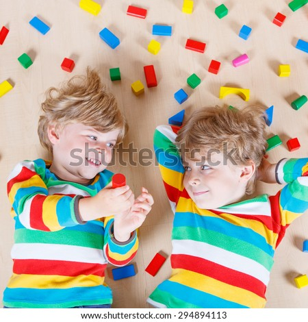 Two little blond friends playing with lots of colorful wooden blocks indoor. Active kid boy wearing colorful shirt and having fun with building and creating. - stock photo