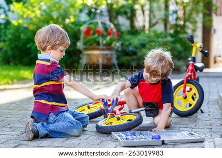 Two little boy friends, twins, learning to repair a bike and to to change a wheel. Siblings working together outdoors, on warm sunny day. Active leisure with kids. - stock photo