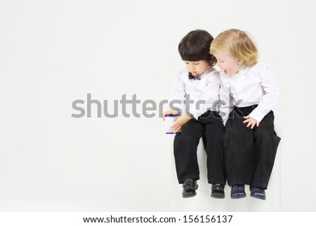Two little boy on white cube play with wireless radio on white background. - stock photo