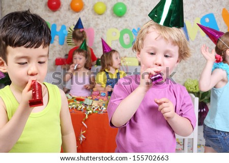 Two little boys blow in multicolor party blowers at birthday party and four girls fun. Inscription Happy Birthday on wall. Focus on boys. - stock photo