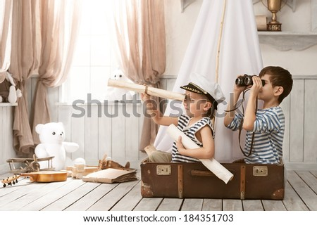 Two little boys in the image of sailors playing in her room  - stock photo
