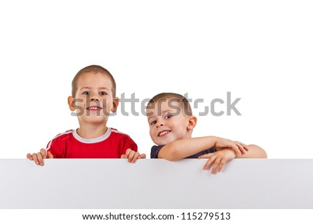 Two little boys look outs from the white board - stock photo