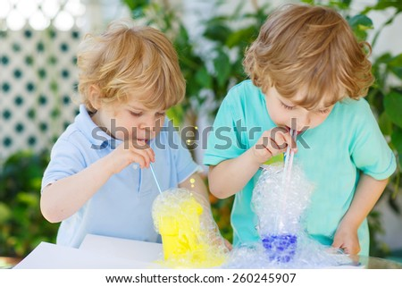 Two little boys making experiment with colorful soap bubbles and water, outdoors. Creative leisure for little kids with water and soap. - stock photo