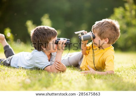 Two little boys play with binoculars on the grass - stock photo