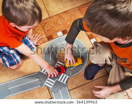 Two little boys plays with toy car - stock photo