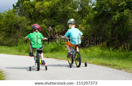 two little boys riding their bikes along a park trail - stock photo
