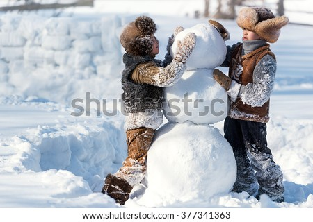 Two little boys sculpt a snowman in the backyard of the house clear winter day - stock photo