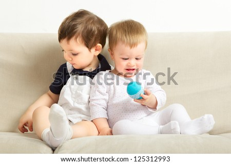 two little boys sitting on couch and playing - stock photo