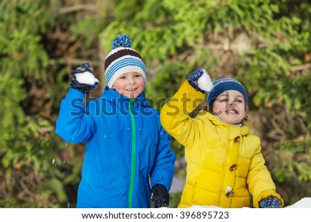 Two little boys with snowballs in the park - stock photo