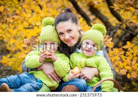 Two little brother and mother on walk in the autumn forest - stock photo