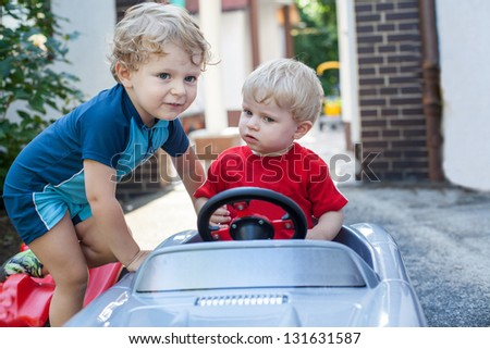 Two little brother toddlers playing with toy car in summer garden - stock photo