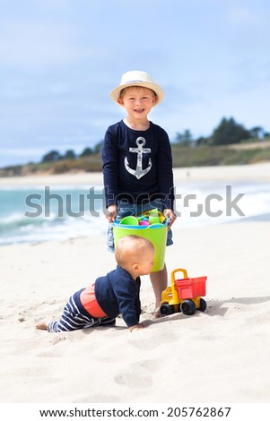 Two little brothers and beach toys  - stock photo
