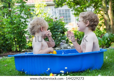 Two little brothers having fun with water in summer garden on sunny day - stock photo